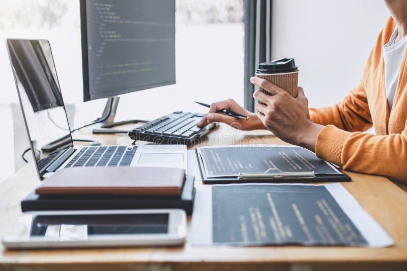 El programador profesional joven que trabaja en la programación que se convierte y la página web que trabaja en un software desar imágenes de archivo libres de regalías