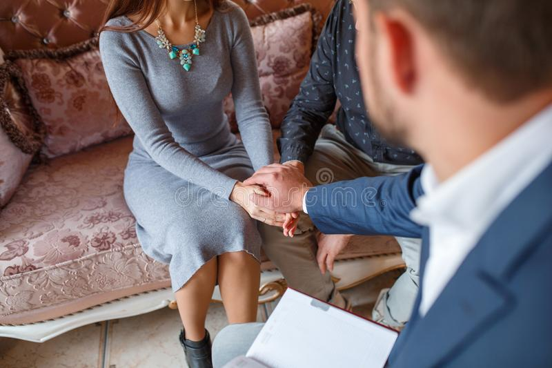 El psicólogo puso su mano en las manos de un par que en la recepción foto de archivo
