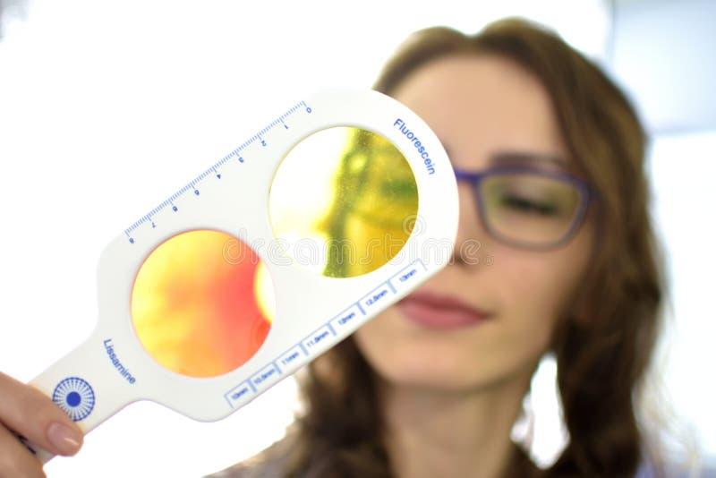 El ?ptico bonito del oftalm?logo del optometrista de la mujer joven realiza una prueba de la acromatopsia fotografía de archivo libre de regalías