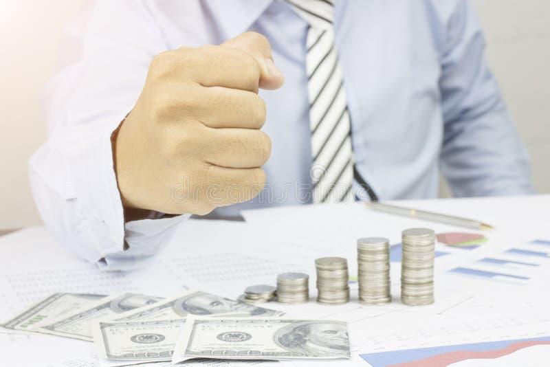 El puño de la demostración del hombre de negocios a seguro y el éxito en negocio en la tabla con el dinero, el papel de trabajo y imagen de archivo libre de regalías