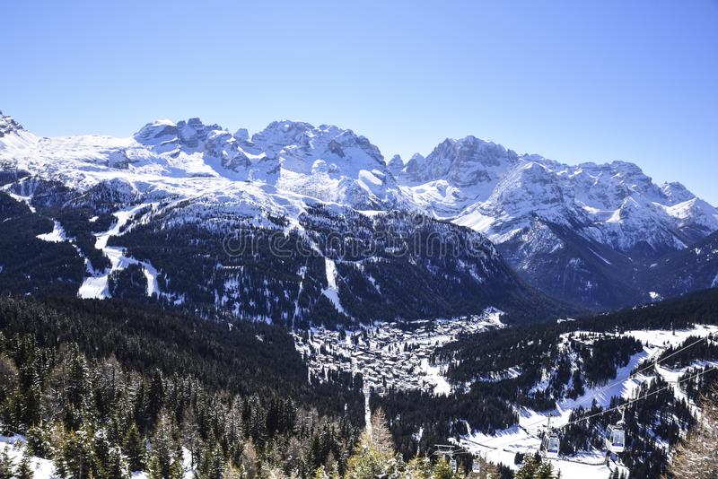 El pueblo de Madonna di Campiglio en el valle, acurrucado entre los picos de las montañas italianas cubiertas con nieve fotografía de archivo libre de regalías