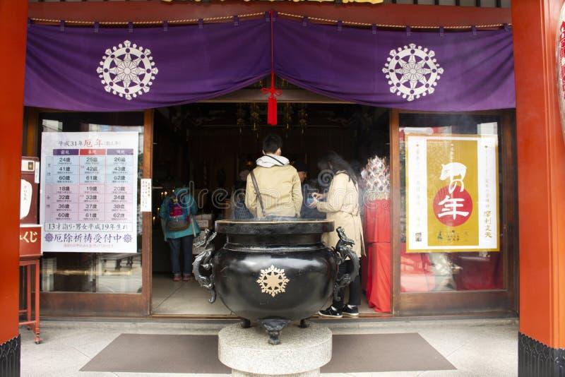 El pueblo japonés ruega dios de Buda y la estatua del ángel dentro del templo de Marishiten Tokudaiji en el mercado de Ameyoko en imagen de archivo libre de regalías