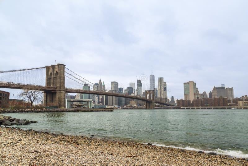 El puente de Brooklyn y bajar Manhattan de vende puerta a puerta la playa en Brooklyn, Nueva York fotografía de archivo libre de regalías