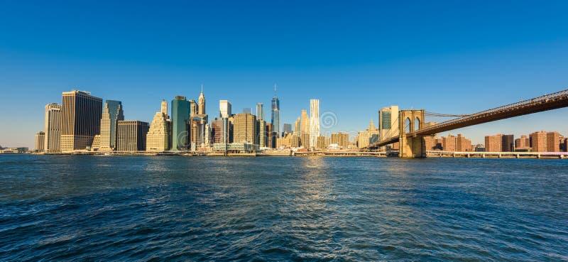 El puente de Brooklyn y el panorama del horizonte del Lower Manhattan del puente de Brooklyn parquean el riverbank, New York City fotografía de archivo