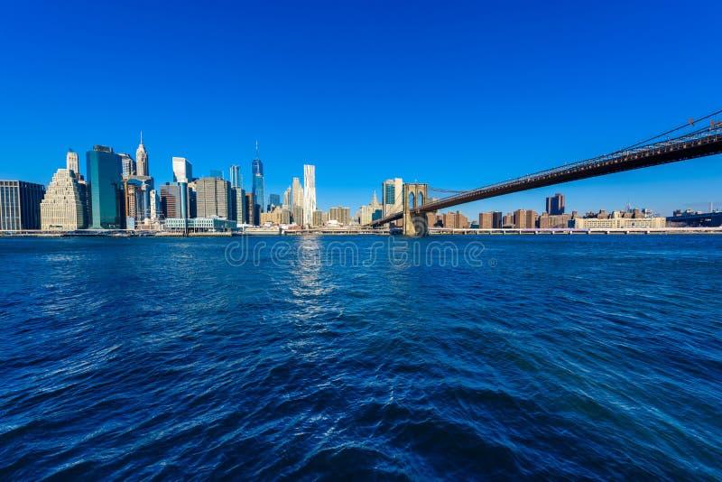 El puente de Brooklyn y el panorama del horizonte del Lower Manhattan del puente de Brooklyn parquean el riverbank, New York City fotografía de archivo libre de regalías