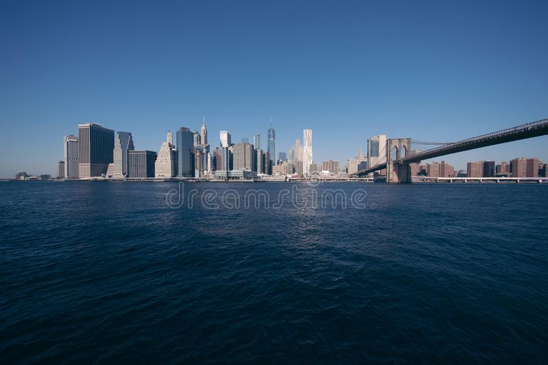 El puente de Brooklyn y el panorama del horizonte del Lower Manhattan del puente de Brooklyn parquean el riverbank, New York City foto de archivo libre de regalías