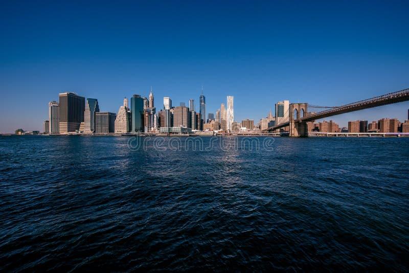 El puente de Brooklyn y el panorama del horizonte del Lower Manhattan del puente de Brooklyn parquean el riverbank, New York City fotos de archivo