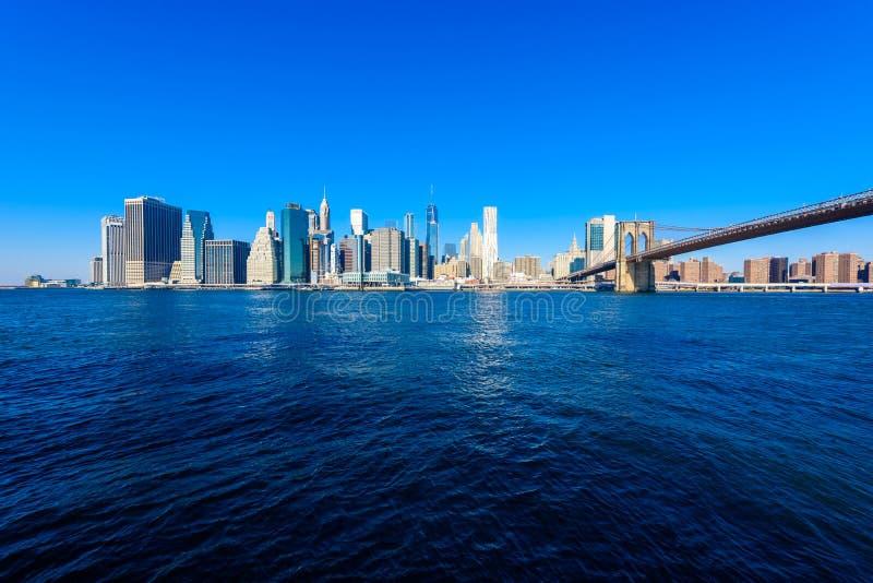 El puente de Brooklyn y el panorama del horizonte del Lower Manhattan del puente de Brooklyn parquean el riverbank, New York City imagenes de archivo