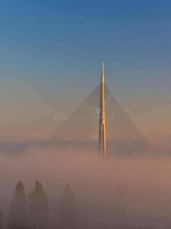 El puente de cable se encendió por la sol sobre la niebla en la salida del sol cerca del Ada en Belgrado imagen de archivo
