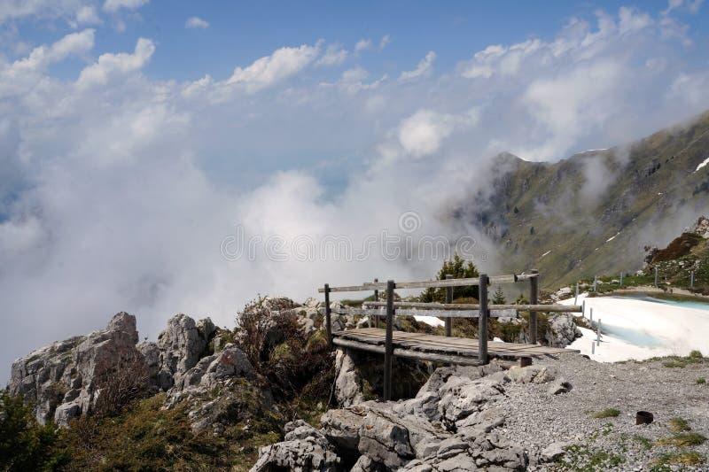 El puente de madera que lleva a las nubes en las montañas suizas fotografía de archivo libre de regalías