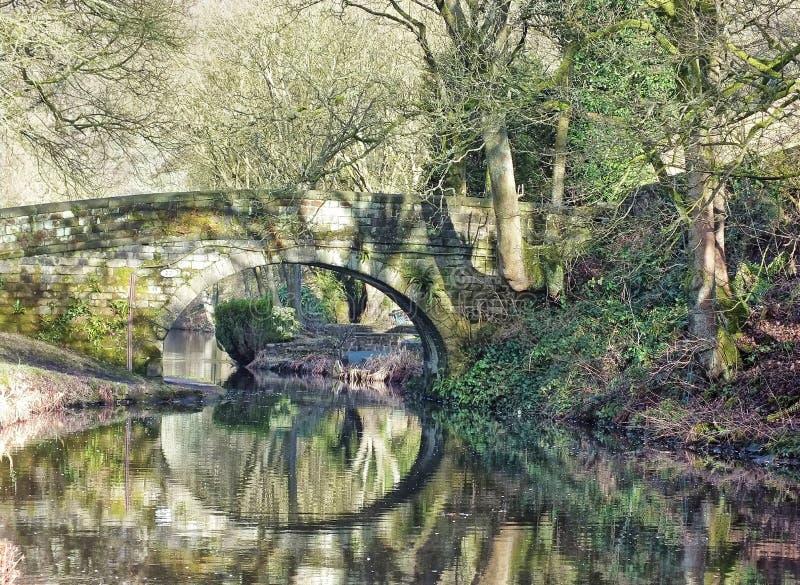 El puente de piedra viejo reflejado en el agua rodeada por el arbolado iluminado por el sol en el canal del rochdale cerca hebden fotografía de archivo