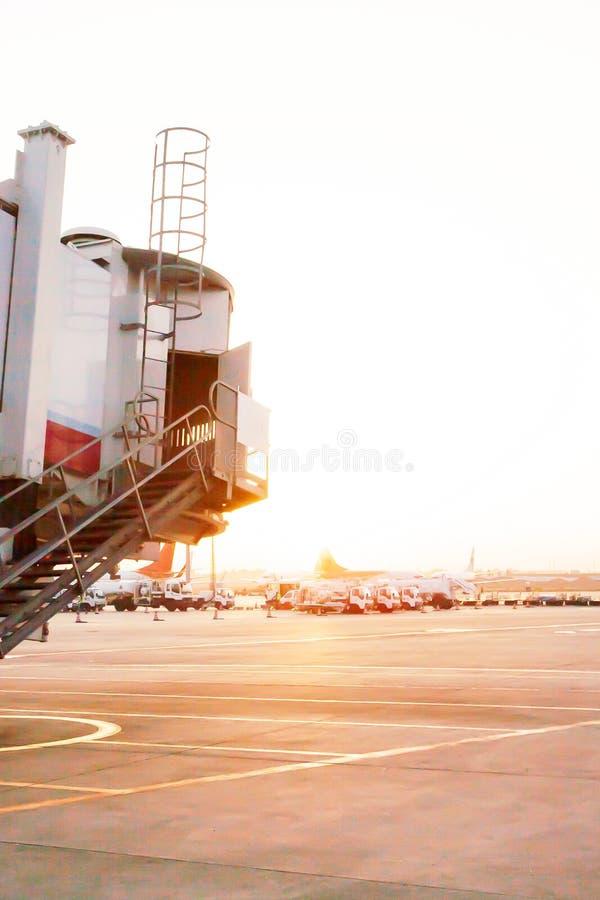 El puente del jet que es movido a un aeroplano en el aeropuerto internacional de Kunming Changshui durante salida del sol fotos de archivo