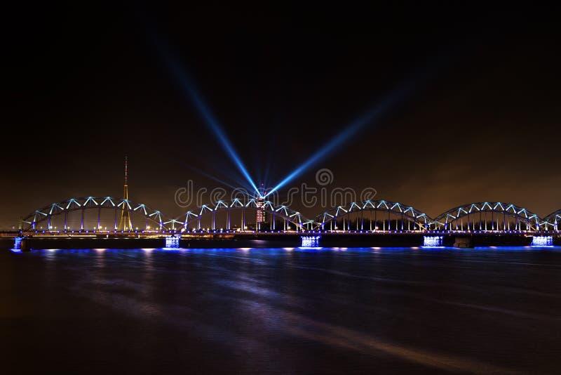 El puente iluminado brillante del ferrocarril, la radio de Riga y la torre de la TV y el edificio letón de la televisión con los  fotos de archivo libres de regalías