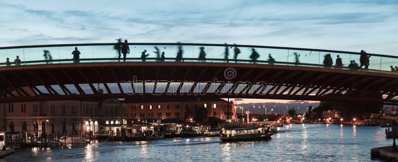 El puente moderno en Venecia en la puesta del sol con las siluetas de los turistas que cruzan un nuevo puente - luz corta - Itali imagen de archivo