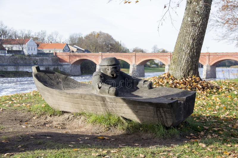El puente viejo del ladrillo a través del río Venta en la ciudad de Kuldiga Letonia y pescador de madera en el barco figura en fr imagen de archivo libre de regalías