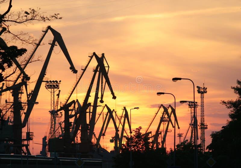El puerto comercial cranes siluetas en la puesta del sol, fondo rojo del cielo imágenes de archivo libres de regalías