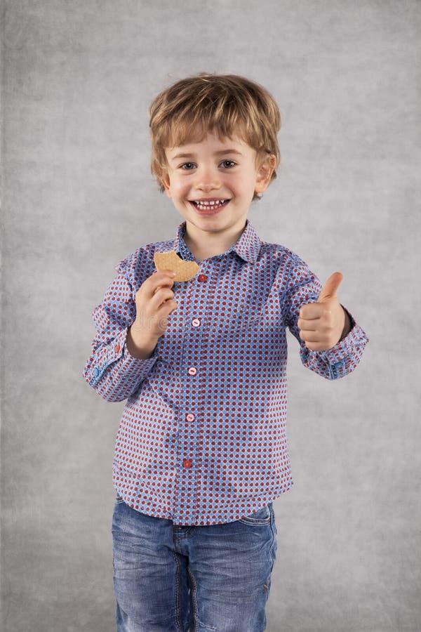 El pulgar para arriba para la galleta agradable, hombre de negocios es un probador fotografía de archivo libre de regalías