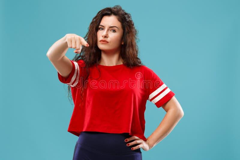 El punto autoritario de la mujer de negocios usted y le quiere, medio retrato del primer de la longitud en fondo azul imagenes de archivo