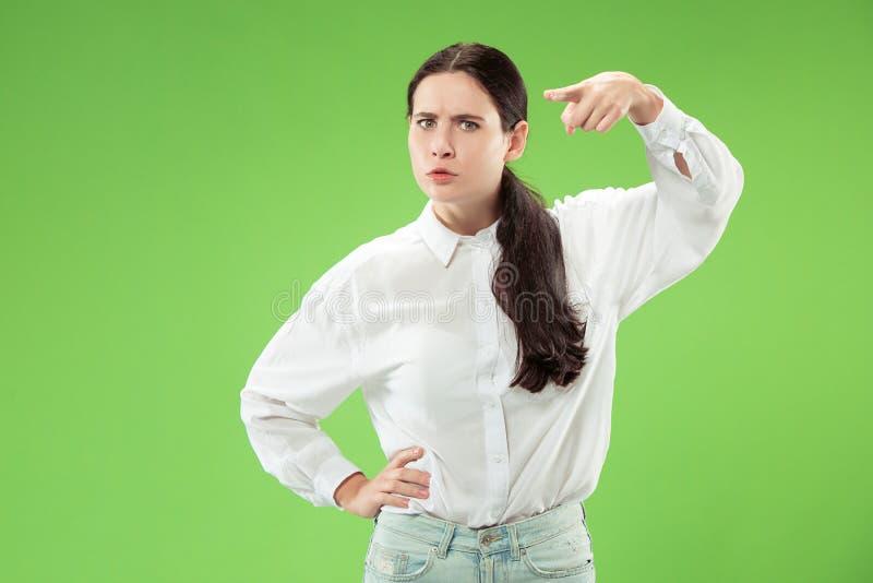 El punto autoritario de la mujer de negocios usted y le quiere, medio retrato del primer de la longitud en fondo verde imagen de archivo