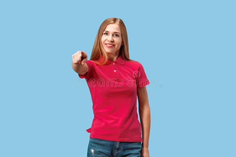 El punto feliz de la mujer de negocios usted y le quiere, medio retrato del primer de la longitud en fondo azul foto de archivo