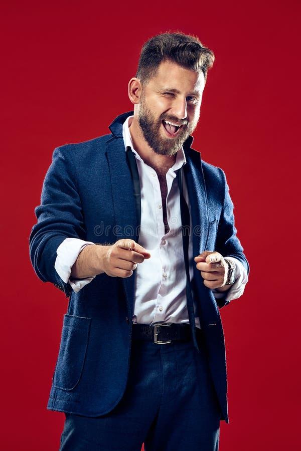 El punto feliz del hombre de negocios usted y le quiere, medio retrato del primer de la longitud en fondo rojo fotos de archivo
