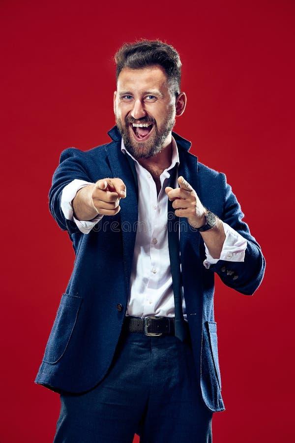 El punto feliz del hombre de negocios usted y le quiere, medio retrato del primer de la longitud en fondo rojo fotografía de archivo libre de regalías