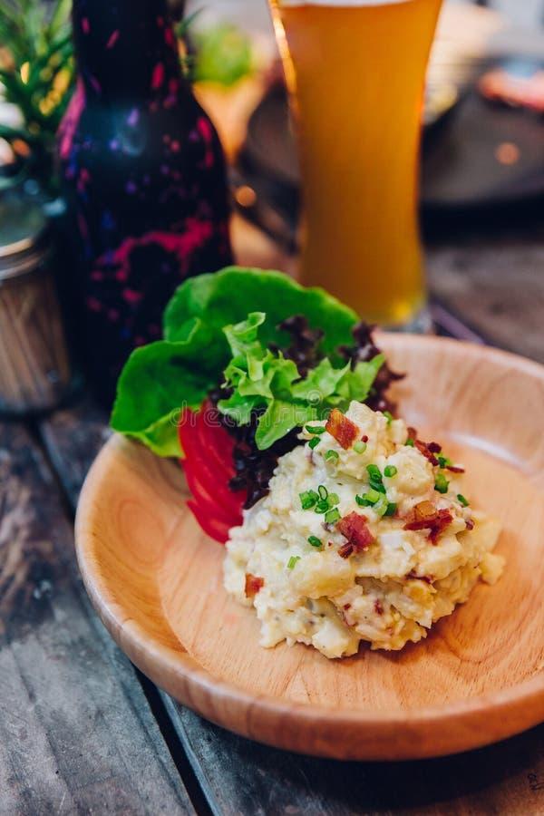 El puré de patata con tocino sirvió con la ensalada en placa de madera con un vidrio de cerveza en el fondo fotografía de archivo libre de regalías