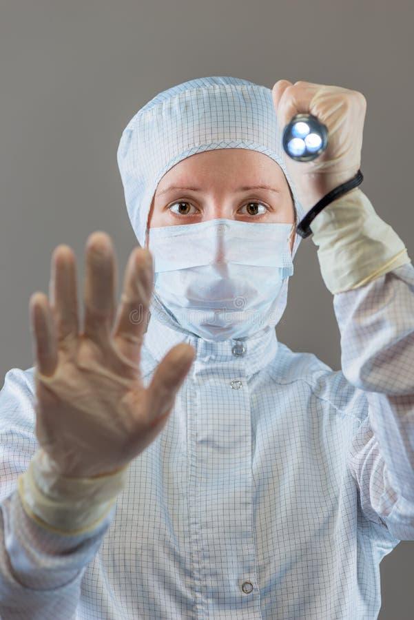 El químico con una linterna muestra la mano del gesto de la PARADA fotografía de archivo