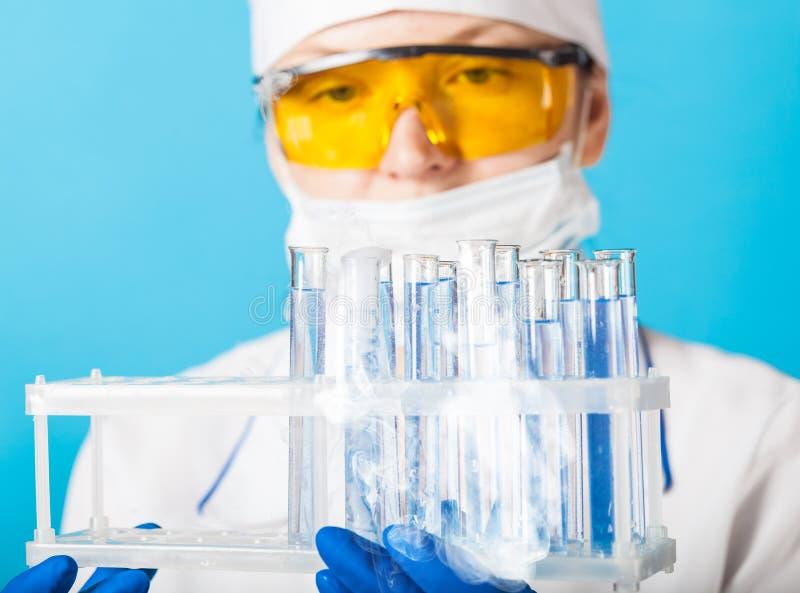 El químico de la mujer examina el tubo de ensayo fotos de archivo libres de regalías