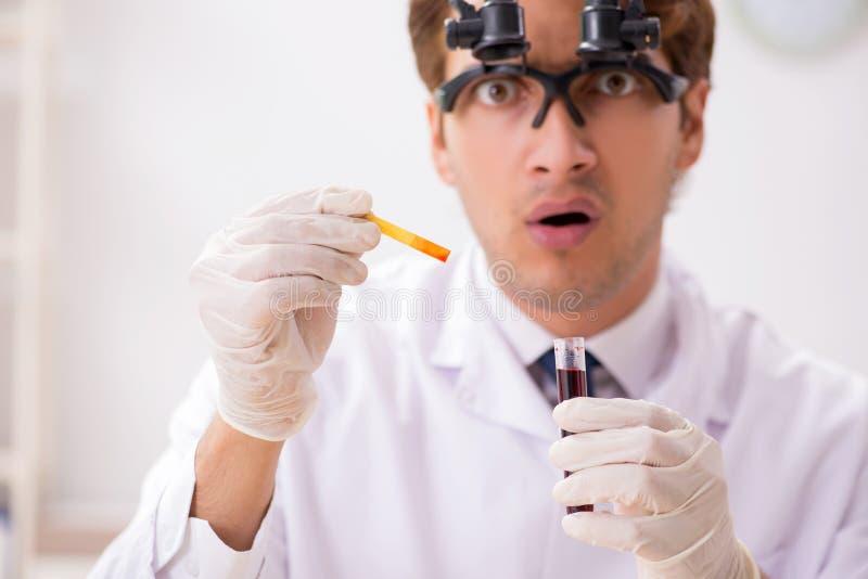 El químico en el laboratorio que comprueba con las tiras del pH fotos de archivo