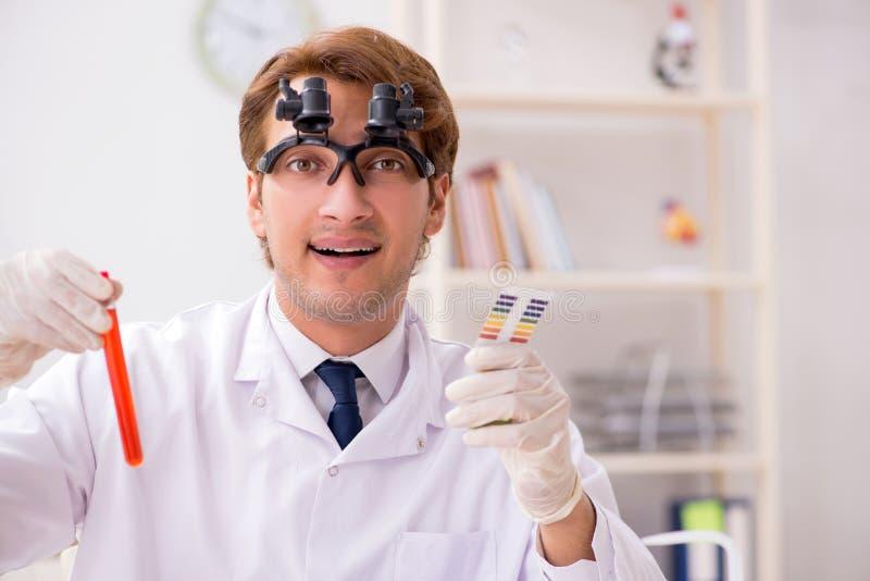 El químico en el laboratorio que comprueba con las tiras del pH imágenes de archivo libres de regalías