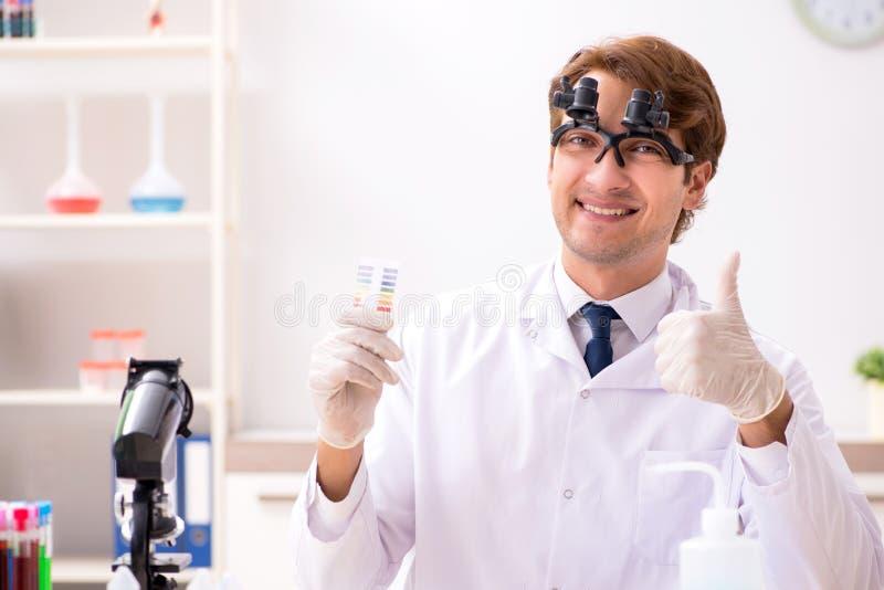 El químico en el laboratorio que comprueba con las tiras del pH foto de archivo libre de regalías