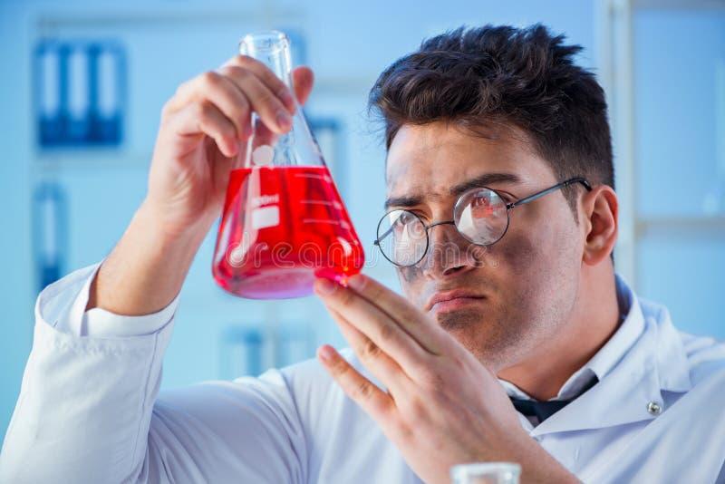 El químico enojado divertido que trabaja en un laboratorio imágenes de archivo libres de regalías