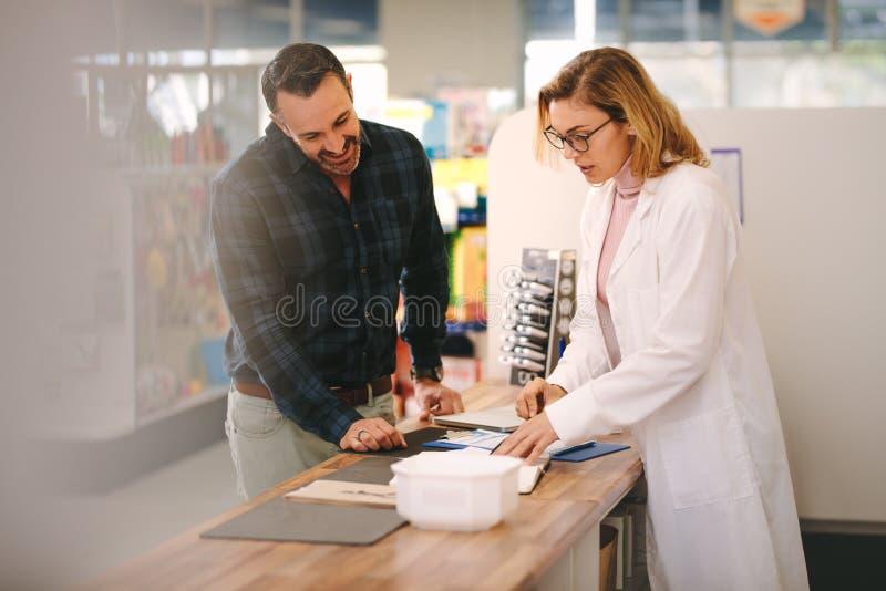 El químico explica una prescripción al cliente fotografía de archivo libre de regalías