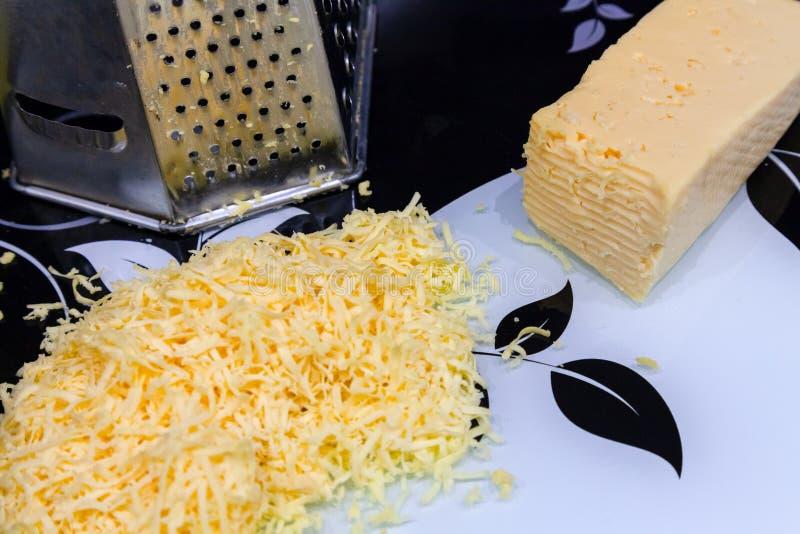 El queso amarillo rallado en una tabla de cortar para cocinar es negro y fotos de archivo