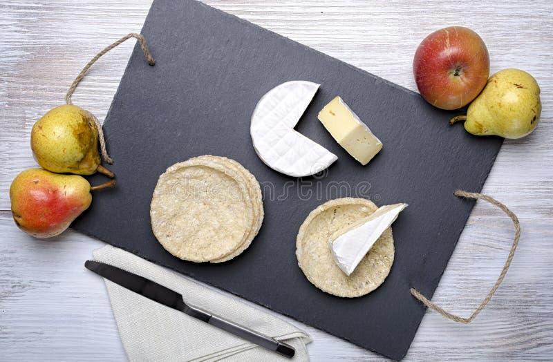 El queso de famille del brie y los pequeños panes redondos mienten en un tablero de la pizarra en un fondo de madera blanco, ques imagenes de archivo