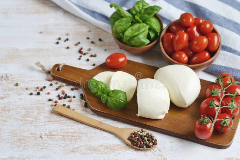 El queso de la mozzarella con los tomates y la albahaca rojos se va, sazona con pimienta, aceite de oliva imagen de archivo