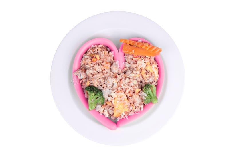 El queso de la salchicha en estilo del corazón envolver el arroz frito con cerdo remató la zanahoria y el bróculi en la placa bla imagenes de archivo