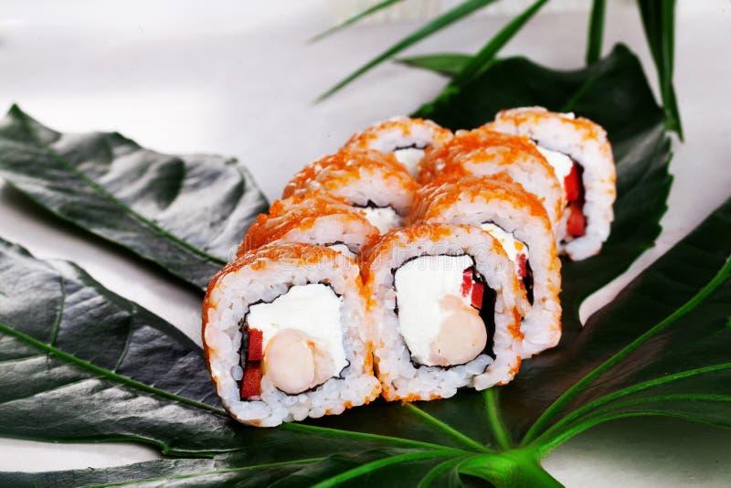 El queso de Philadelphia del camarón del rojo anaranjado del rollo de sushi de Masago, vida de la pimienta dulce todavía en el tr fotos de archivo libres de regalías
