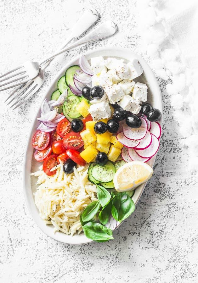 El queso Feta, orzo, tomates, pepinos, rábanos, aceitunas, sazona la ensalada con pimienta en un fondo ligero, visión superior co imagen de archivo