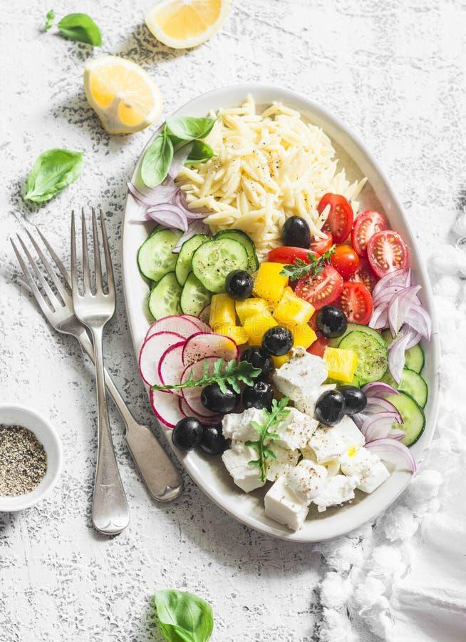 El queso Feta, orzo, tomates, pepinos, rábanos, aceitunas, sazona la ensalada con pimienta en un fondo ligero, visión superior Co imagen de archivo libre de regalías