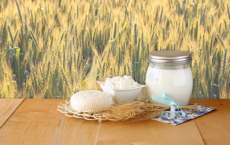 El queso, la cabaña y la leche de Tzfatit en la tabla de madera sobre campo de trigo en el sol de la salida del sol estallaron el foto de archivo