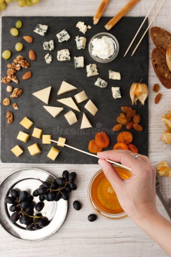 El queso y la fruta se mezclan en la piedra negra con la mano de la mujer fotografía de archivo