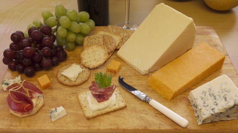 El queso y las galletas sirvieron en una tarjeta de madera imagenes de archivo