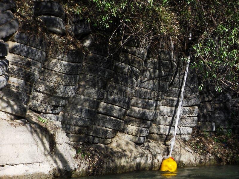 El río Ak-Buura el cercado de los neumáticos a la casa bajó en el río imagenes de archivo