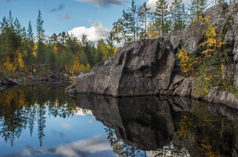 El río fluye entre las rocas y el bosque del taiga fotos de archivo