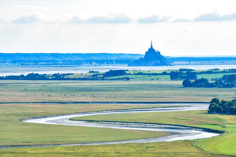 El río hace su manera entre los campos y las tierras de labrantío hasta Mont Saint Michel imagen de archivo