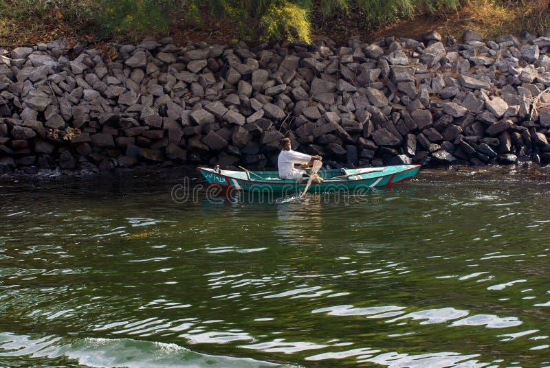 El río Nilo, cerca de Asuán, el 16 de febrero de 2017: pescador que se bate en un bote pequeño en el dio, vestido en el blanco eg foto de archivo libre de regalías