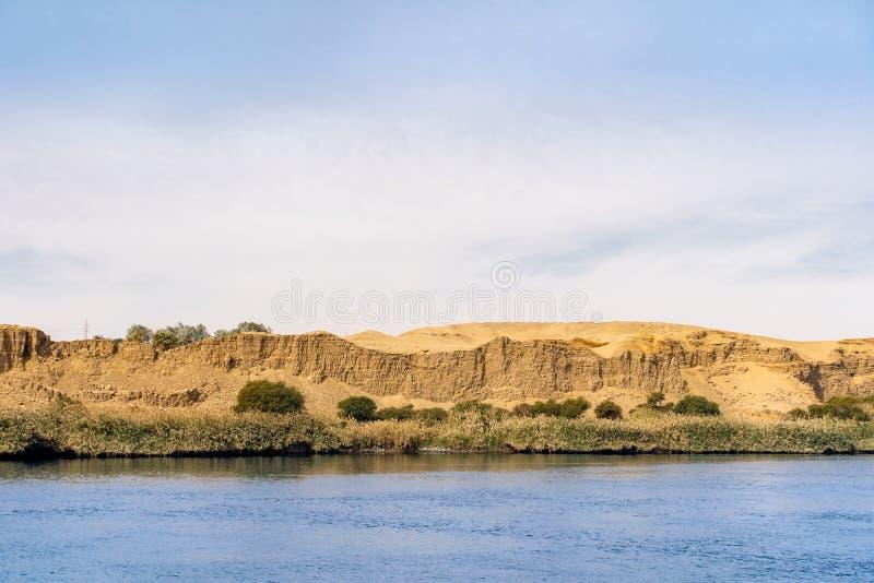 El río el Nilo con él es orillas del río llenas de vegetaion y del cierre de Sahara Desert cerca fotografía de archivo