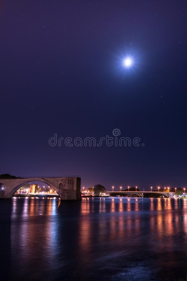 El río Rhone durante noche con el puente de Benezet del santo y la ciudad se encienden fotografía de archivo